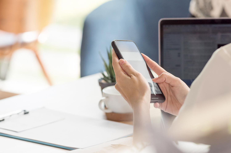 femme professionnelle - business women avec un smartphone cabinet fontanès digitalise ses missions grâce à des applications mobiles bureau avec un ordinateur et un smartphone